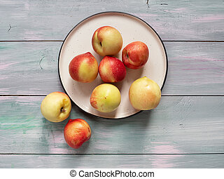 ripe nectarines in a ceramic plate on a light wooden background