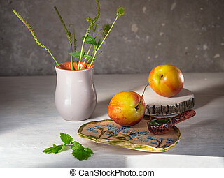 Ripe nectarines on a white background with ceramic dishes and meadow herbs in a ceramic gray vase