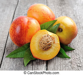 Ripe nectarines with leaves .