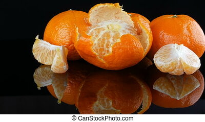 Ripe orange tangerines on a mirror surface on a black...