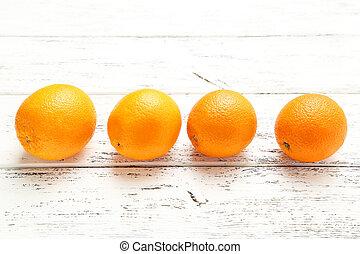 Ripe oranges on white wooden background