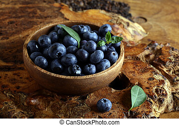ripe organic blueberries in a wooden bowl