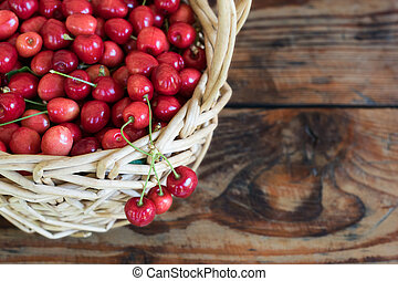 Ripe organic homegrown cherries in a basket, on wooden...