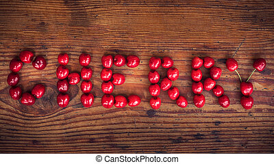 Ripe organic homegrown cherries on wooden background, Cherry text