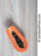 Ripe papaya with copyspace on wooden background.
