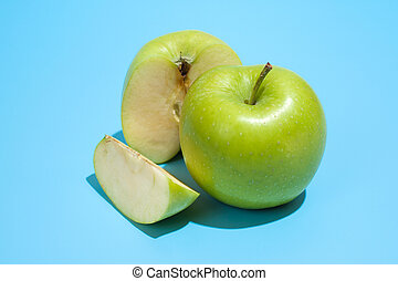 Ripe parts green apple Isolated on a blue background. Healthy eating and dieting concept