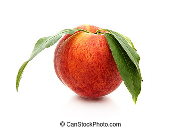 Ripe peach with green leaves.