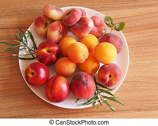 Ripe peaches and apricots on a white plate and a wooden background