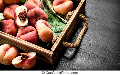 Ripe peaches in a wooden box.