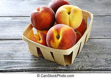 ripe peaches in wooden box
