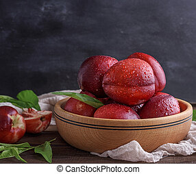 ripe peaches nectarine in a brown wooden bowl, behind a...