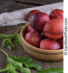 ripe peaches nectarine in a brown wooden bowl,  close up