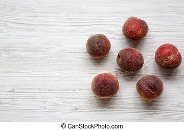 Ripe peaches on white wooden background, top view. Copy space.