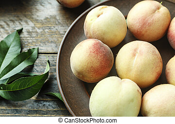 ripe peaches with leaves on the table