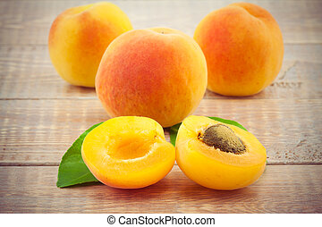 Ripe peaches with leaves on wooden table