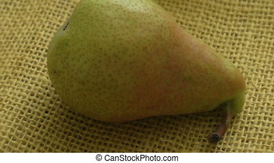 Ripe pear on yellow background. European pear with sack...