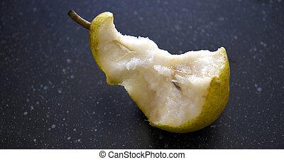 ripe pear,half eaten on dark blue background