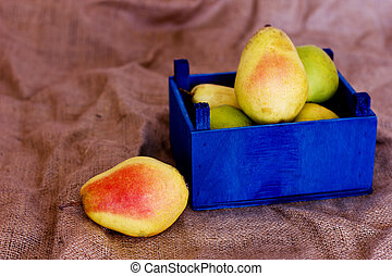 Ripe pears in a blue wooden box.