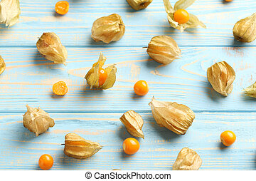 Ripe physalis on a blue wooden table