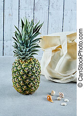 Ripe pineapple and white bag on blue background with seashells
