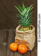 Ripe pineapple in paper bag with oranges on wooden table.