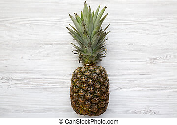 Ripe pineapple on a white wooden background. From above. Top view.