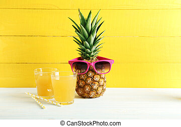 Ripe pineapple with glasses of juice on a white wooden table