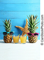 Ripe pineapples with glasses of juice on a white wooden table