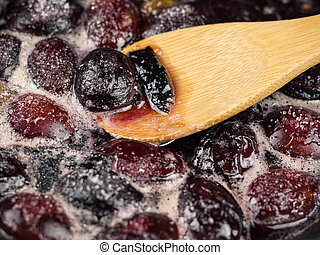 Ripe plums are cooked in sugar syrup and mix with a wooden spoon.