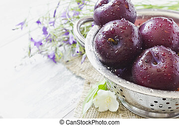 ripe plums in a colander closeup and wild flowers on the table. selective focus. health and diet food