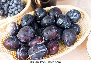 ripe plums in a plate on the table