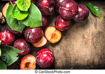 Ripe plums in a wooden tray.