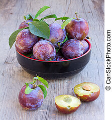 ripe plums in black plate on the old gray board close-up, side view