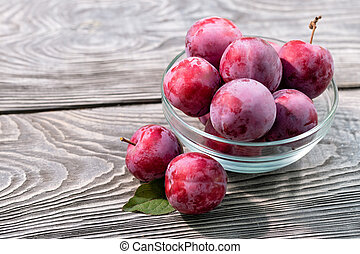 Ripe plums in glass bowl on wooden table