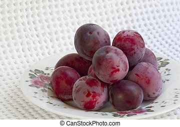 Ripe plums on a plate