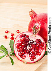 Ripe pomegranate fruit with green leaf.