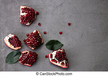 Ripe pomegranate fruits on a dark background, top view with copy space