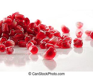 Ripe pomegranate seeds on white
