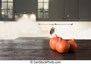Ripe pumpkin on wooden tabletop in modern kitchen. Space for design. Thanksgiving day.