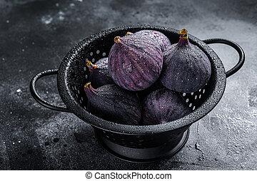 Ripe purple Figs in colander. Black background. Top view