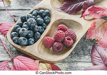 Ripe raspberries and blueberries with red beautiful autumn leaves. Close-up.