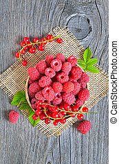 Ripe raspberries and redcurrants on wooden table
