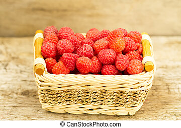 ripe raspberries in the basket on wooden
