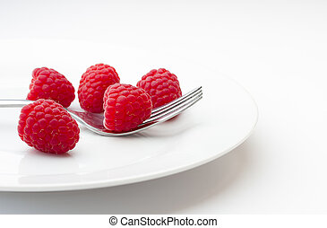 Ripe raspberries on a plate with fork