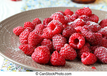 ripe raspberries on a plate with icing sugar, food close up