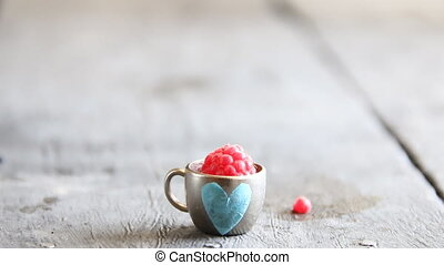 ripe raspberry in a cup with heart, place for text - ripe...