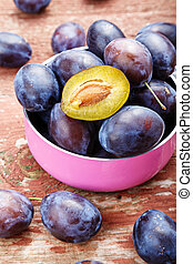 Ripe raw plums in a pink saucepan on a wooden background