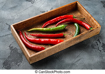 Ripe Red and green chili pepper, in wooden box, on gray background