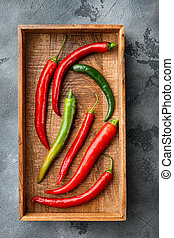 Ripe Red and green chili pepper, in wooden box, on gray background, top view flat lay