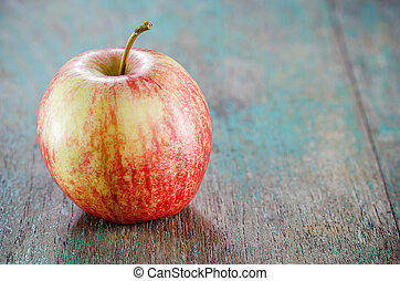 Ripe red apple on wooden background